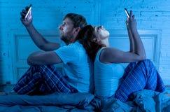 Pares en cama en los teléfonos móviles que se ignoran en problemas de la relación y el apego de la tecnología foto de archivo