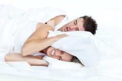 Pares en cama mientras que la mujer está intentando dormir Foto de archivo libre de regalías