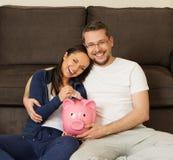 Pares en casa con el piggybank Imagenes de archivo