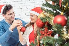 Pares en casa que adornan el árbol para la Navidad Imágenes de archivo libres de regalías