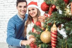 Pares en casa que adornan el árbol para la Navidad Imagenes de archivo