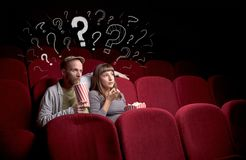 Pares en cine con preguntas Imagenes de archivo