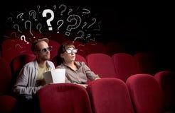 Pares en cine con preguntas Fotografía de archivo libre de regalías