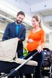 Pares en cochecito de la compra de tienda del bebé Imagen de archivo libre de regalías