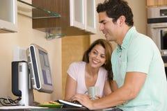 Pares en cocina con la sonrisa del ordenador y del café Imagenes de archivo