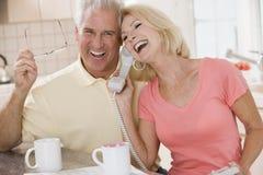 Pares en cocina usando el teléfono junto Foto de archivo libre de regalías