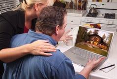 Pares en cocina usando la computadora portátil - cabina Foto de archivo