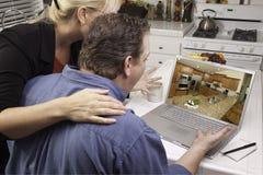 Pares en cocina usando la computadora portátil - mejoras para el hogar Foto de archivo
