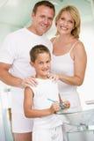 Pares en cuarto de baño con los dientes que aplican con brocha del muchacho joven Imágenes de archivo libres de regalías