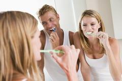 Pares en dientes que aplican con brocha del cuarto de baño Fotografía de archivo libre de regalías