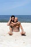 Pares en el abrazo de la playa Imágenes de archivo libres de regalías