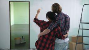 Pares en el abrazo del amor que mira la pared pintada almacen de metraje de vídeo