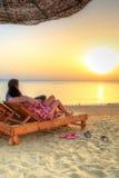 Pares en el abrazo que mira junta la salida del sol en el bea Foto de archivo libre de regalías