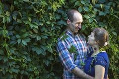 Pares en el amor que abraza entre el verdor Foto de archivo libre de regalías