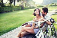 Pares en el amor que bromea junto en un banco con las bicis imágenes de archivo libres de regalías
