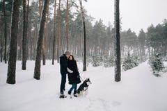 Pares en el amor que camina con el perro esquimal en bosque del invierno Fotografía de archivo libre de regalías