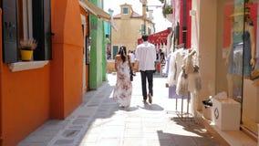 Pares en el amor que camina llevando a cabo las manos a lo largo de ventanas coloreadas de la tienda en la calle