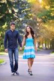 Pares en el amor que da un paseo junto en un parque hermoso Imagen de archivo