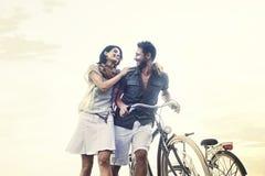 Pares en el amor que empuja la bicicleta junto foto de archivo