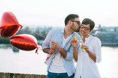 Pares en el amor que lleva a cabo corazones rojos de los baloons el día de San Valentín Imagen de archivo