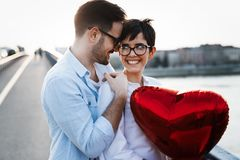 Pares en el amor que lleva a cabo corazones rojos de los baloons el día de San Valentín Fotos de archivo libres de regalías