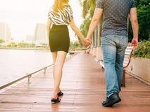 Pares en el amor que lleva a cabo las manos con uno a en el embarcadero Imágenes de archivo libres de regalías