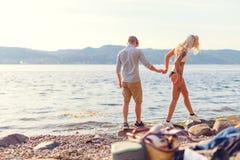 Pares en el amor que lleva a cabo las manos y que camina en la playa Imágenes de archivo libres de regalías