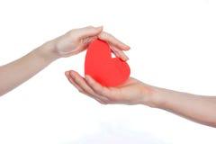 Pares en el amor que lleva a cabo un corazón de papel rojo en sus manos aisladas en el fondo blanco Imagen de archivo