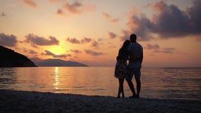 Pares en el amor que se abraza que se coloca en una playa en la puesta del sol sobre el mar almacen de video