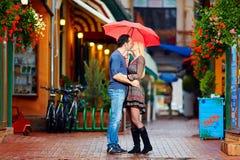 Pares en el amor que se besa debajo de la lluvia Foto de archivo libre de regalías