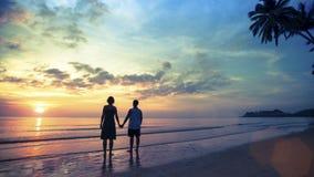 Pares en el amor que se coloca en la costa que mira una puesta del sol maravillosa Imágenes de archivo libres de regalías