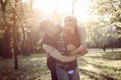 Pares en el amor que se coloca en parque y el abrazo imágenes de archivo libres de regalías