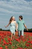 Pares en el amor que se ejecuta a través de campo de la amapola Fotografía de archivo
