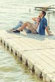 Pares en el amor que se sienta en el embarcadero, abrazo Fotografía de archivo