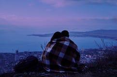 Pares en el amor que se sienta en la colina sobre la ciudad en noche Fotos de archivo