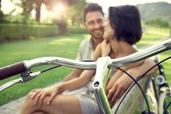 Pares en el amor que se sienta junto en un banco con las bicis fotos de archivo