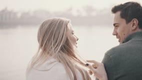 Pares en el amor que se sienta en la hierba y que abraza en un parque metrajes