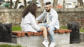 Pares en el amor que se sienta en un banco en un parque que se mira almacen de metraje de vídeo