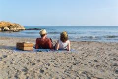 Pares en el amor que tiene una comida campestre en una playa mediterránea en la puesta del sol fotos de archivo