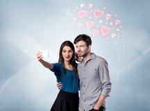 Pares en el amor que toma el selfie con el corazón rojo Imagen de archivo libre de regalías