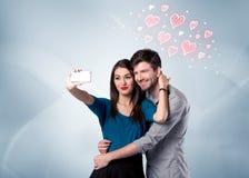 Pares en el amor que toma el selfie con el corazón rojo Imágenes de archivo libres de regalías