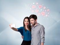 Pares en el amor que toma el selfie con el corazón rojo Fotografía de archivo
