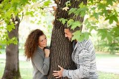 Pares en el bosque otoñal, mirando a escondidas de detrás un árbol Imágenes de archivo libres de regalías