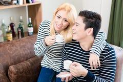 Pares en el café de consumición del sofá junto Imagen de archivo libre de regalías