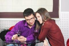 Pares en el café que mira el teléfono celular Foto de archivo libre de regalías