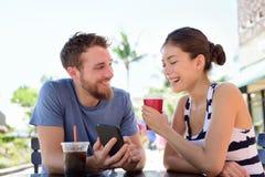 Pares en el café que mira imágenes elegantes del app del teléfono Fotografía de archivo