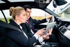Pares en el coche que es navegación perdida con el mapa Foto de archivo libre de regalías