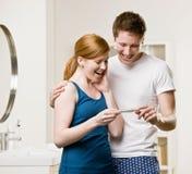 Pares en el cuarto de baño que ve tes positivos del embarazo Imagenes de archivo