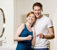 Pares en el cuarto de baño que ve tes positivos del embarazo Foto de archivo