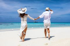 Pares en el funcionamiento blanco de la ropa del verano feliz en una playa tropical imagenes de archivo